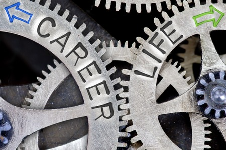 career life: Macro photo of tooth wheel mechanism with arrows and CAREER, LIFE concept words