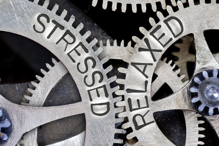 destress: Macro photo of tooth wheel mechanism with arrows and STRESSED, RELAXED letters