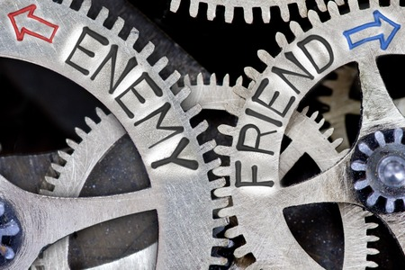 foe: Macro photo of tooth wheel mechanism with arrows and ENEMY, FRIEND concept words Stock Photo