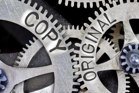 copycat: Macro photo of tooth wheel mechanism with COPY, ORIGINAL concept words