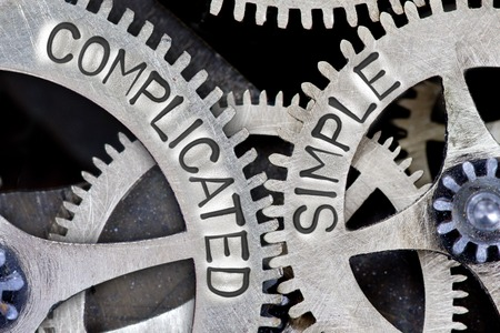 complicated: Macro photo of tooth wheel mechanism with COMPLICATED, SIMPLE concept words Stock Photo