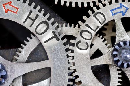 Makro-Foto von Zahnradmechanismus mit Pfeilen und HOT, COLD Konzept Worte