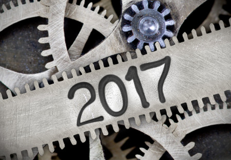 imprinted: Macro photo of tooth wheel mechanism with number 2017 imprinted on clean metal surface; New Year concept
