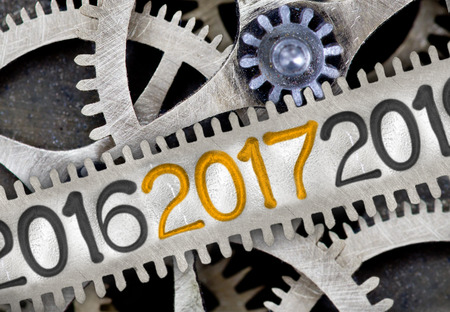 imprinted: Macro photo of tooth wheel mechanism with numbers 2016, 2017, 2018 imprinted on clean metal surface; New Year concept