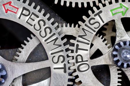 pessimist: Macro photo of tooth wheel mechanism with imprinted arrows and PESSIMIST, OPTIMIST concept words