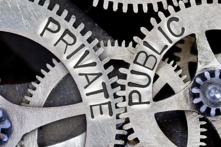 Fotografía macro del mecanismo de la rueda dentada con flechas y letras PÚBLICAS PRIVADAS