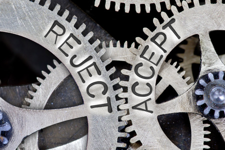 approvement: Macro photo of tooth wheel mechanism with REJECT, ACCEPT letters