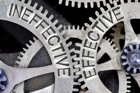 ineffective: Macro photo of tooth wheel mechanism with INEFFECTIVE, EFFECTIVE concept words