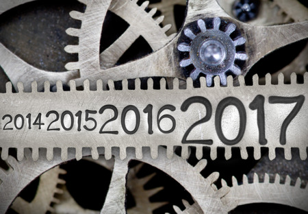 imprinted: Macro photo of tooth wheel mechanism with numbers 2014, 2015, 2016, 2017 imprinted on clean metal surface; New Year concept Stock Photo