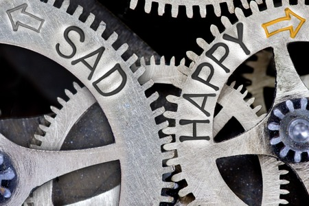 imprinted: Macro photo of tooth wheel mechanism with imprinted arrows and SAD, HAPPY concept words
