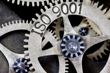 standard steel: Macro photo of tooth wheel mechanism with ISO 9001 concept letters Stock Photo