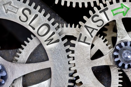 slower: Macro photo of tooth wheel mechanism with imprinted arrows and SLOW, FAST concept words