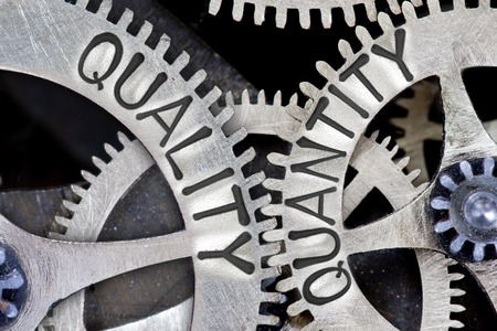 imprinted: Macro photo of tooth wheel mechanism with imprinted QUALITY, QUANTITY concept words Stock Photo