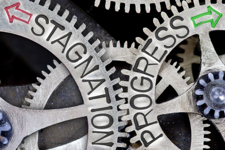 imprinted: Macro photo of tooth wheel mechanism with imprinted arrows and STAGNATION, PROGRESS concept words