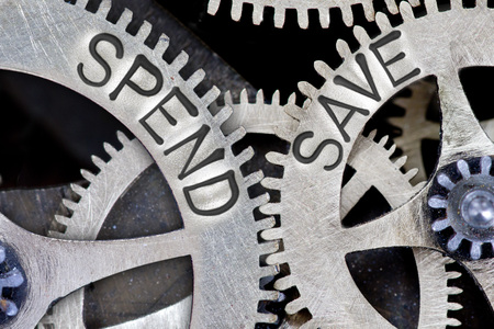 balanced budget: Macro photo of tooth wheel mechanism with imprinted arrows and SPEND, SAVE concept words Stock Photo