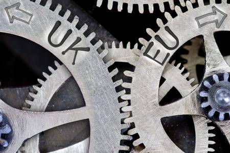 imprinted: Macro photo of tooth wheel mechanism with imprinted arrows and UK, EU concept words