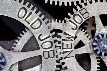 imprinted: Macro photo of tooth wheel mechanism with imprinted OLD JOB, NEW JOB concept words