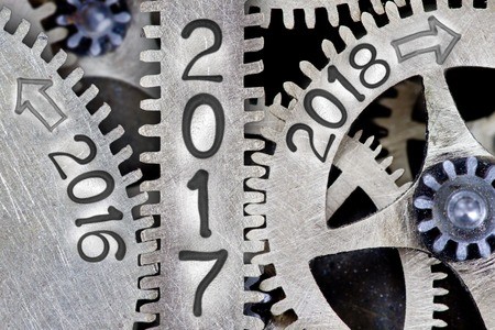 Macro photo of tooth wheel mechanism with numbers 2016, 2017, 2018 imprinted on clean metal surface; New Year concept