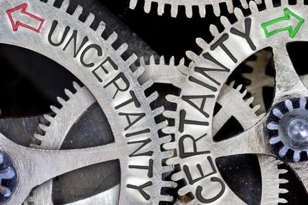 validez: foto macro de mecanismo de rueda dentada con las flechas y la incertidumbre impresos, las palabras conceptuales CERTEZA Foto de archivo