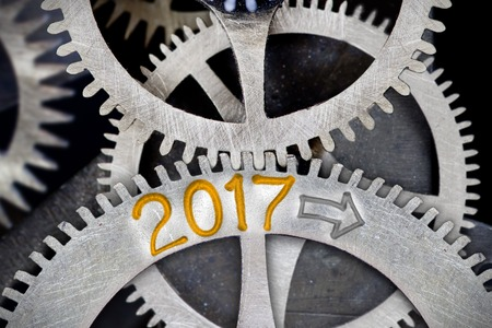 Macro photo of tooth wheel mechanism with number 2017 imprinted on clean metal surface; New Year concept