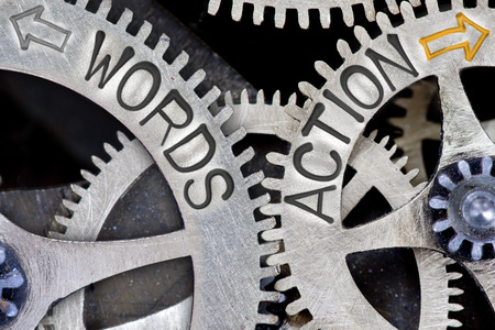 imprinted: Macro photo of tooth wheel mechanism with imprinted arrows and WORDS, ACTION concept words Stock Photo