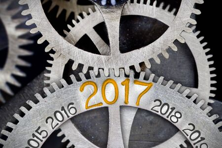 Macro photo of tooth wheel mechanism with numbers 2015, 2016, 2017, 2018 and 2019 imprinted on clean metal surface; New Year concept