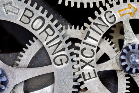 imprinted: Macro photo of tooth wheel mechanism with imprinted arrows and BORING, EXCITING concept words