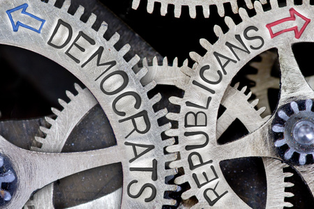 imprinted: Macro photo of tooth wheel mechanism with imprinted arrows and DEMOCRATS, REPUBLICANS concept words