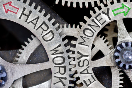 imprinted: Macro photo of tooth wheel mechanism with imprinted arrows and HARD WORK, EASY MONEY concept words Stock Photo