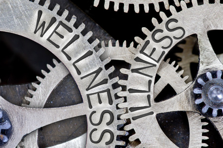 imprinted: Macro photo of tooth wheel mechanism with imprinted WELLNESS, ILLNESS concept words