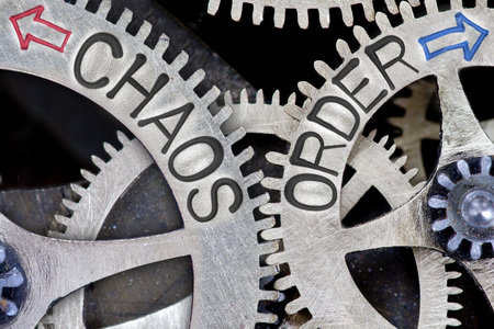 chaos: Macro photo of tooth wheel mechanism with imprinted arrows and CHAOS, ORDER concept words Stock Photo