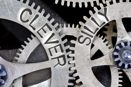 capable of learning: Macro photo of tooth wheel mechanism with imprinted CLEVER, SILLY concept words Stock Photo