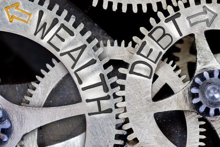 imprinted: Macro photo of tooth wheel mechanism with imprinted arrows and WEALTH, DEBT concept words Stock Photo