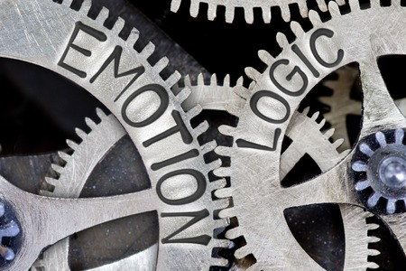 Macro photo of tooth wheel mechanism with imprinted EMOTION, LOGIC concept words