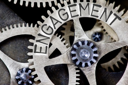 Macro photo of tooth wheel mechanism with ENGAGEMENT concept letters 스톡 콘텐츠