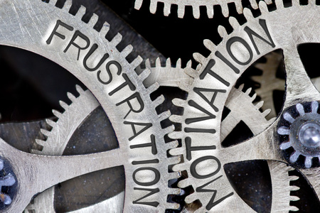 imprinted: Macro photo of tooth wheel mechanism with imprinted arrows and FRUSTRATION, MOTIVATION concept words Stock Photo