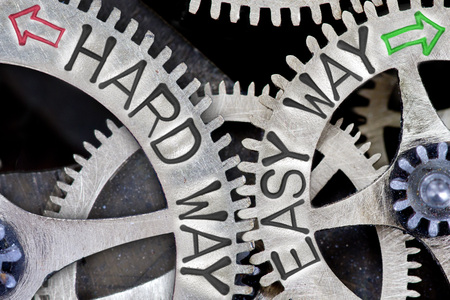 imprinted: Macro photo of tooth wheel mechanism with imprinted arrows and HARD WAY, EASY WAY concept words