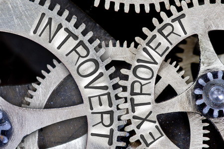 inhibited: Macro photo of tooth wheel mechanism with imprinted INTROVERT, EXTROVERT concept words