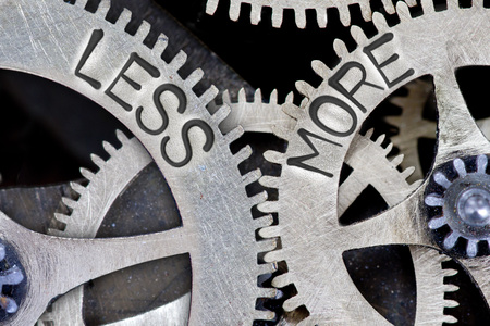 imprinted: Macro photo of tooth wheel mechanism with imprinted LESS, MORE concept words Stock Photo