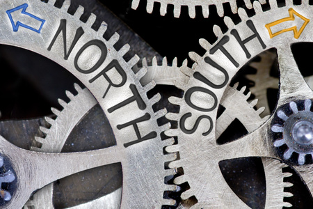 imprinted: Macro photo of tooth wheel mechanism with imprinted arrows and NORTH, SOUTH concept words Stock Photo