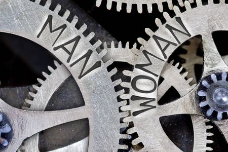 challenging sex: Macro photo of tooth wheel mechanism with imprinted MAN, WOMAN concept words Stock Photo
