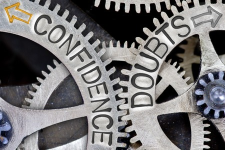 imprinted: Macro photo of tooth wheel mechanism with imprinted arrows and CONFIDENCE, DOUBTS concept words Stock Photo