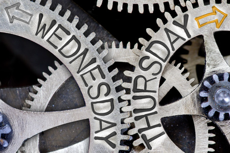 wednesday: Macro photo of tooth wheel mechanism with imprinted arrows and WEDNESDAY, THURSDAY concept words Stock Photo