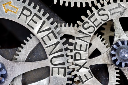 imprinted: Macro photo of tooth wheel mechanism with imprinted arrows and REVENUE, EXPENSES concept words