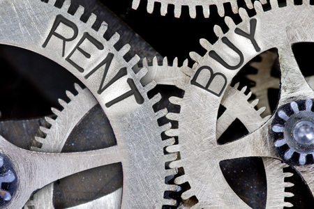 imprinted: Macro photo of tooth wheel mechanism with imprinted RENT, BUY concept words