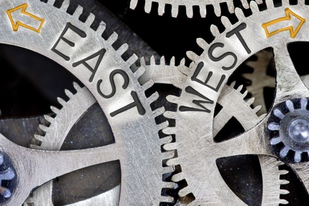 imprinted: Macro photo of tooth wheel mechanism with imprinted arrows and EAST, WEST concept words Stock Photo