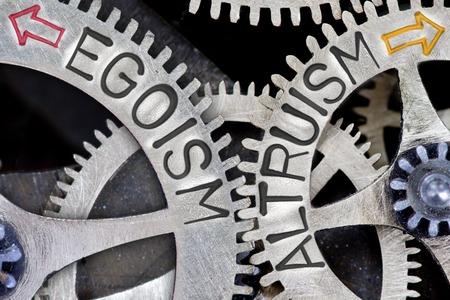 altruismo: foto macro de mecanismo de rueda dentada con las flechas y el egoísmo impresos, palabras del concepto de altruismo