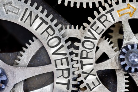 inhibited: Macro photo of tooth wheel mechanism with imprinted arrows and INTROVERT, EXTROVERT concept words Stock Photo