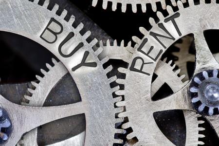 vs: Macro photo of tooth wheel mechanism with imprinted BUY, RENT concept words