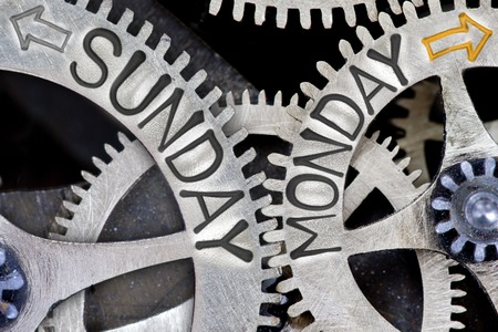 imprinted: Macro photo of tooth wheel mechanism with imprinted arrows and SUNDAY, MONDAY concept words